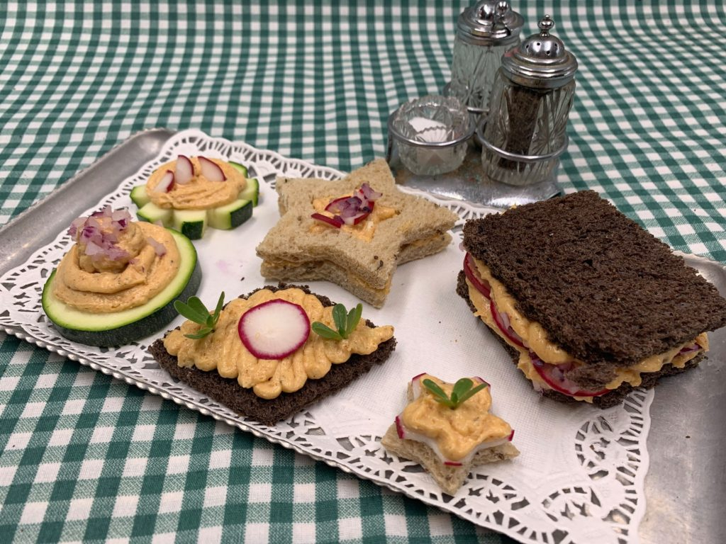 Small finger sandwiches made of sliced bread and cucumbers with Bavarian cheese spread and garnishes on top, placed on a metal serving tray with a plaid green background.