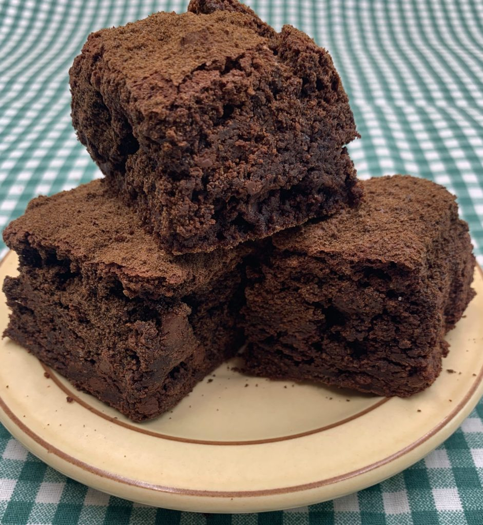 Three pumpernickel brownies stacked like a pyramid on a beige plate with a green plaid background.